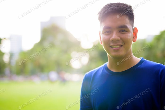 Young handsome Asian man relaxing at the park