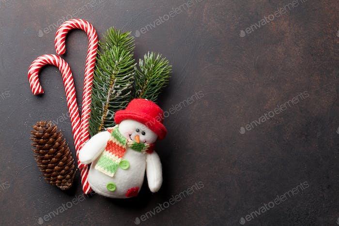 Christmas candy canes, snowman toy and fir tree