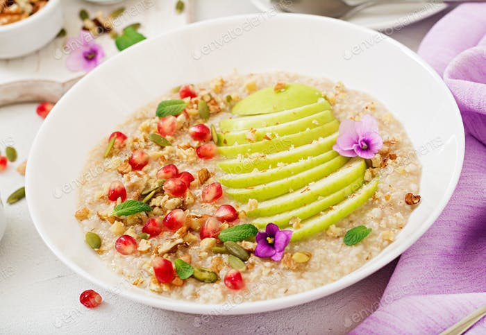 Tasty and healthy oatmeal porridge with apples, pomegranate and nuts.