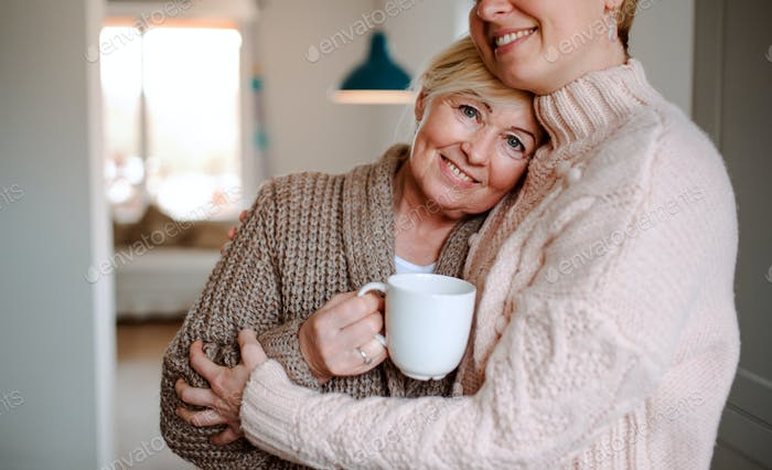 A senior woman with unrecognizable daughter at home, hugging.