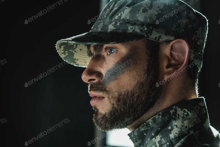 close-up portrait of thoughtful young soldier with camouflage on face