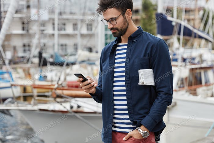 Cropped shot of hipster guy in fashionable clothes, carries newspaper, has stroll across harbour in