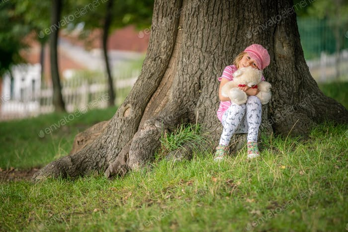 Girl sitting under a tree holding teddy bear
