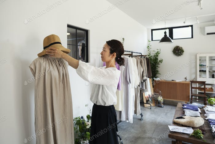 Japanese women standing in a small fashion boutique, arranging hat on mannequin.