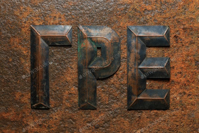 Aged embossed copper cyrillic letters on rusty surface