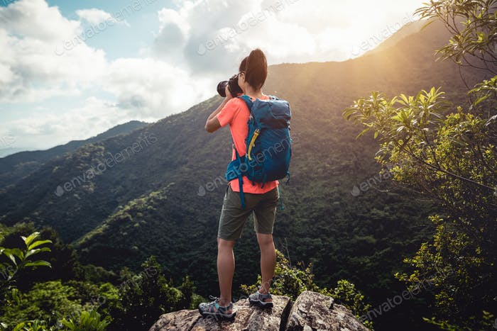 Photographer taking pictures on top of summer mountains