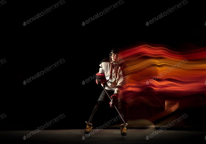 Young female hockey player with the stick on black background in neon light