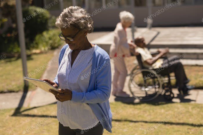 Front view of senior woman using digital tablet in garden on a sunny day