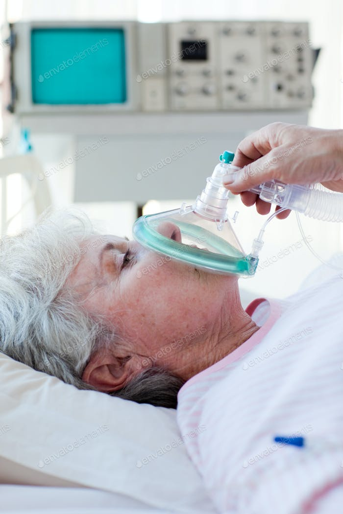 Senior patient receiving oxygen mask