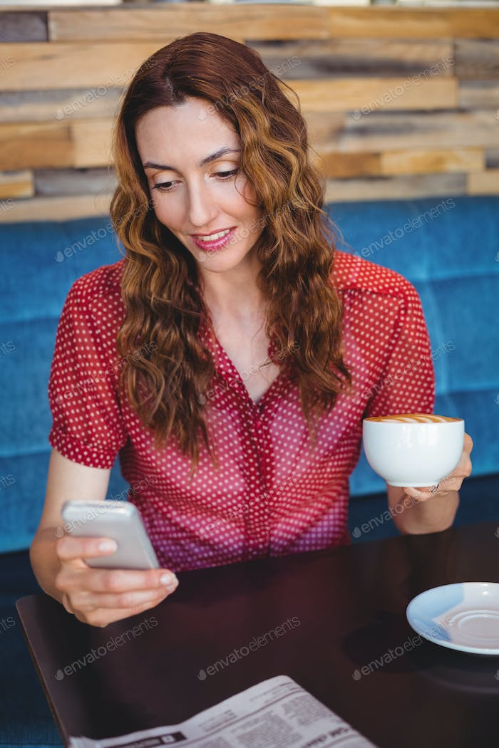 Woman using her mobile phone and holding cup of coffee at the coffee shop