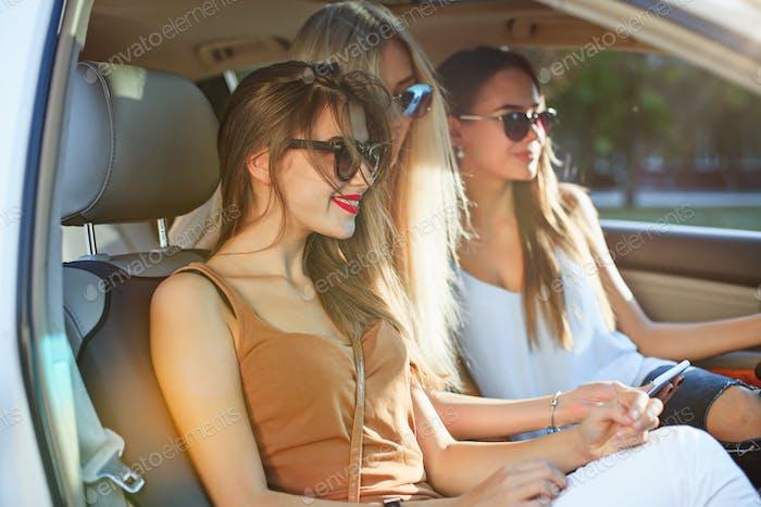 Las chicas europeas bonitas 25-30 años de edad en el coche hacen fotos en el teléfono Móvil