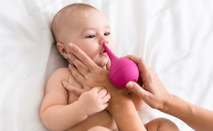 Newborn baby getting nose cleaning with cleaner