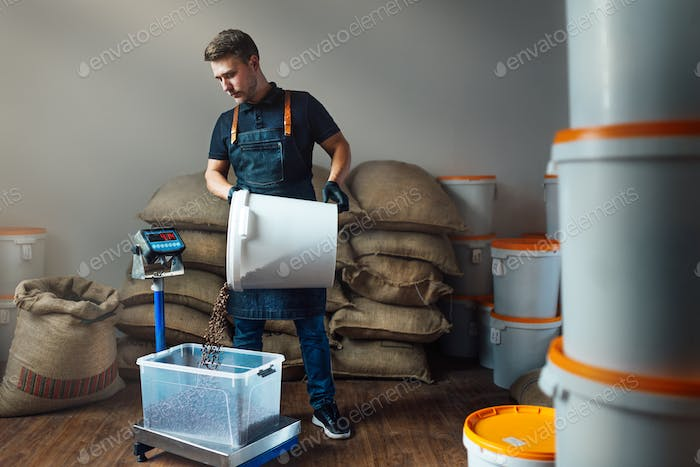 worker in uniform pours roasted coffee from white bucket into tray