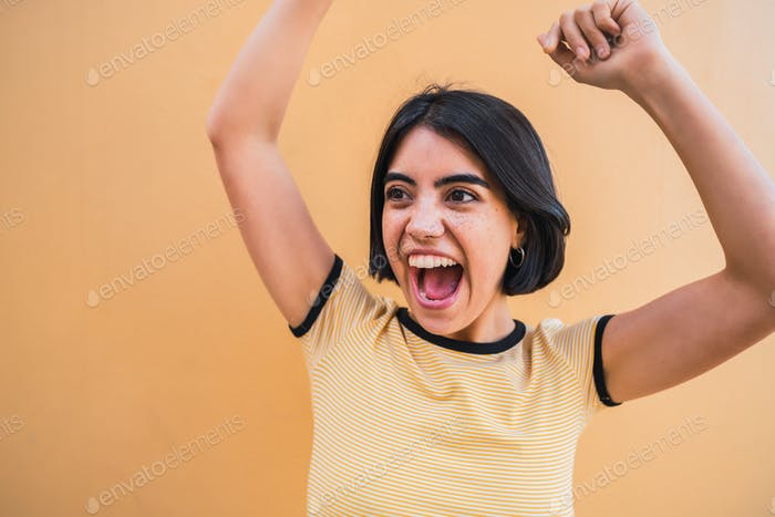 Young woman celebrating victory on yellow wall