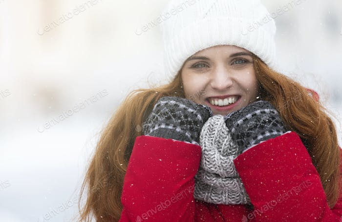 Cheerful young girl in warm clothes enjoying snowy winter day