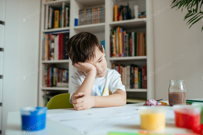 Tired child getting sleep on table with colorful paints.