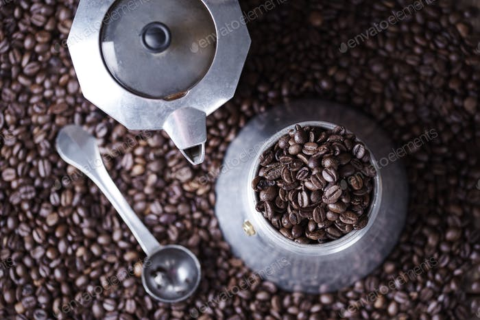 Old fashioned coffee grinder among coffee beans