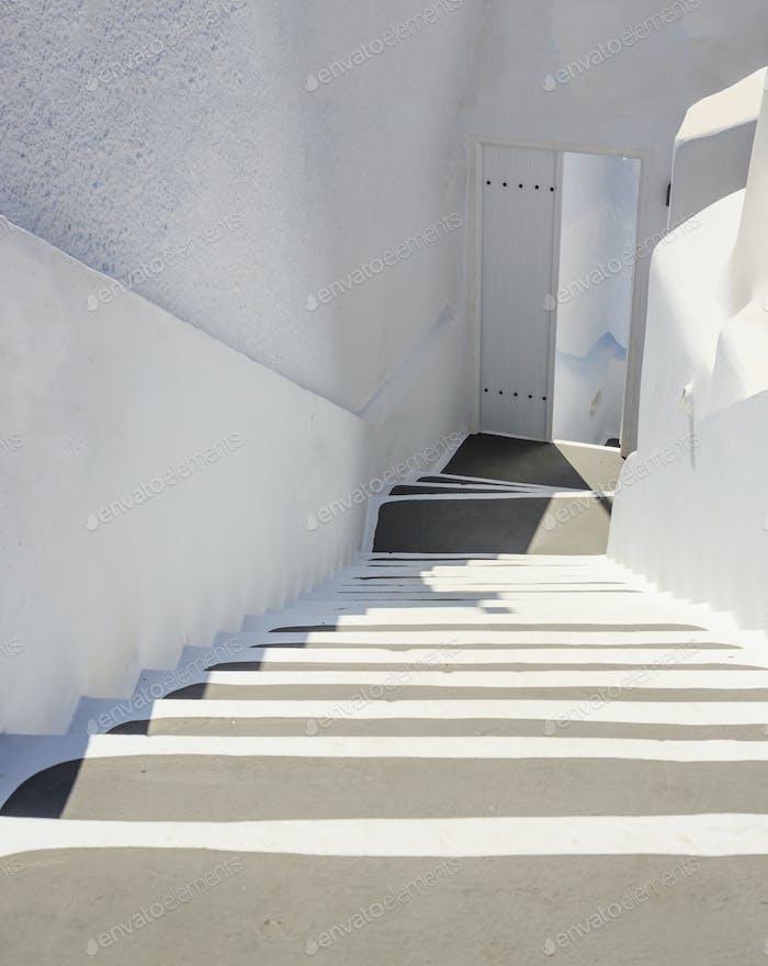 Santorini, Greece. White architecture, staircase going down to an open door.