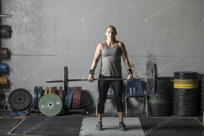 Strong woman powerlifter training in gym.