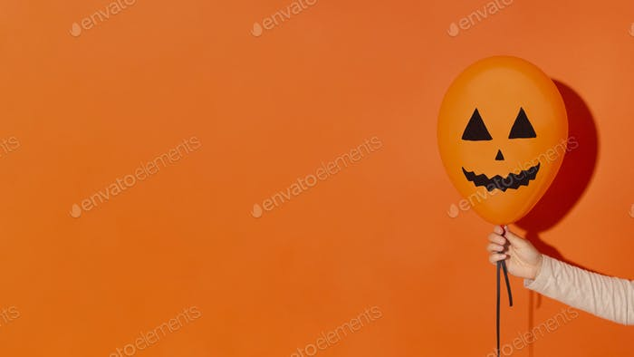 Woman holding party balloon with face on orange background