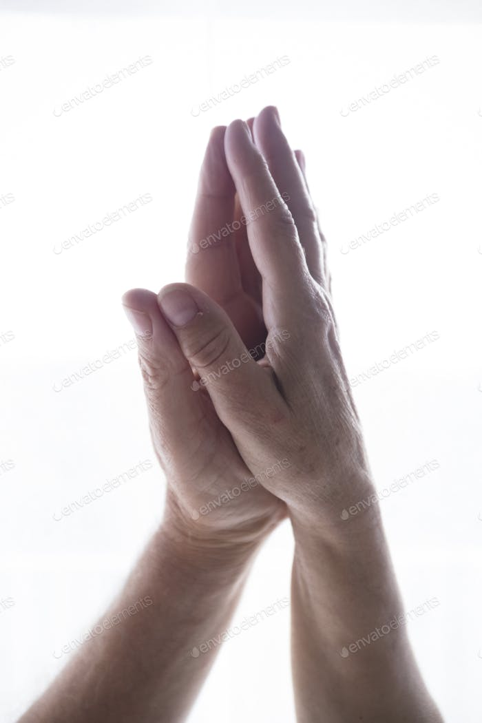Palm of human hands joined together in namaste prayer position over white copy space