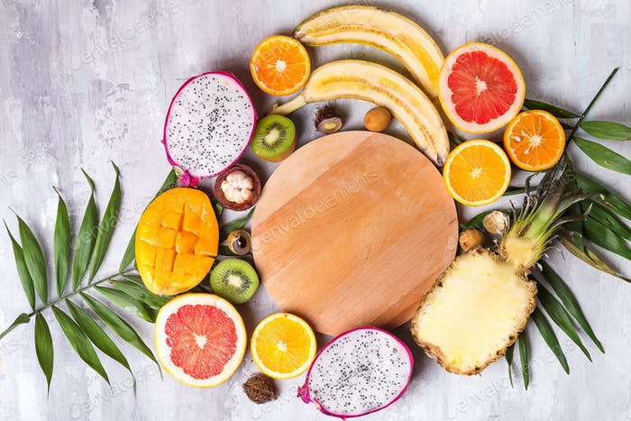 Fruits and palm leaves on stone background with wooden plate. Tropical fruits. Summer concept. Flat