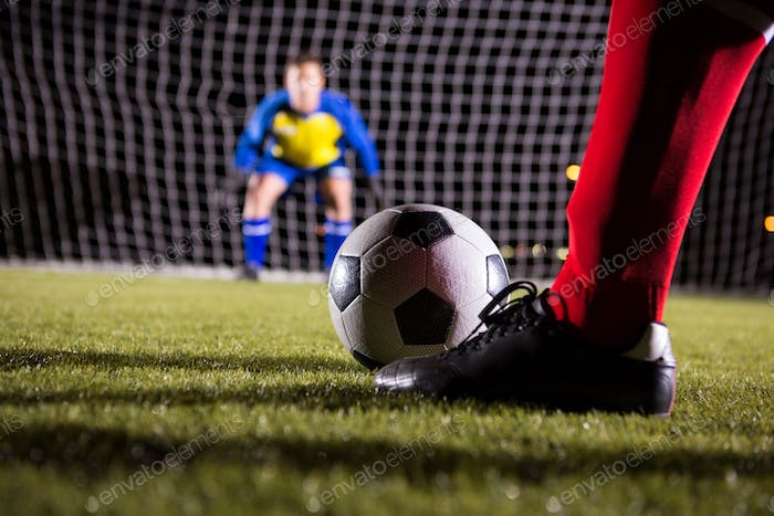Low section of soccer player with ball against goalkeeper