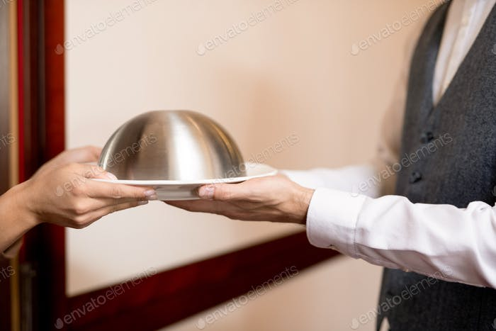 Hands of young woman taking cloche with restaurant food from elegant waiter