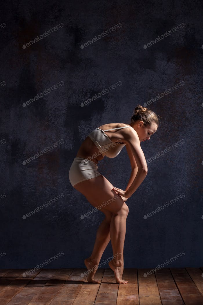 Young beautiful dancer in beige swimwear dancing on lilac background