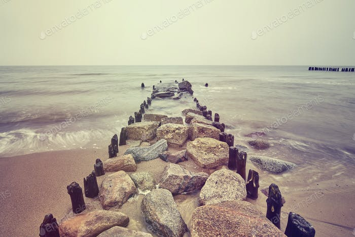 Vintage toned picture of an old breakwater on cloudy day