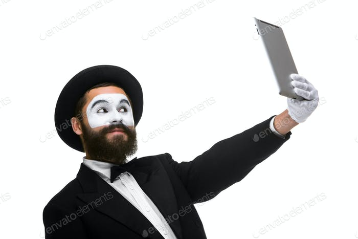 Man with a face mime working on a laptop isolated on a white background.