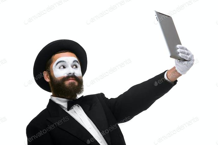 Mann mit einem Gesicht Pantomime arbeitet an einem Laptop isoliert auf einem weißen Hintergrund.