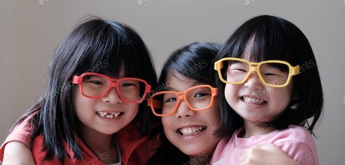 Three children wear big eyeglasses