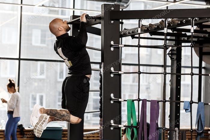 Brutaler athletischer Mann in schwarzer Art Kleidung zieht sich in der Turnhalle an die Bar