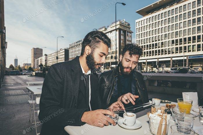 Zwei junge bärtige kaukasische moderne Geschäftsmann sitzt in einer Bar