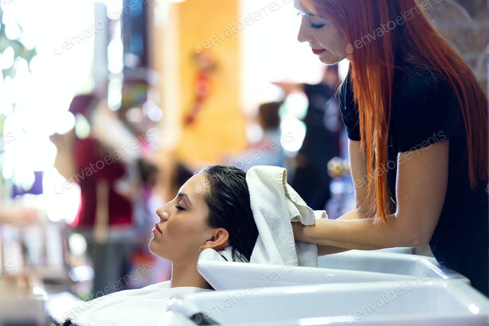 The hairdresser wraps the client's hair in a towel after washing
