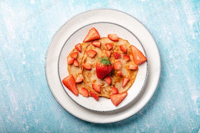Pfannkuchen mit frischer Erdbeere auf einem blauen hölzernen Hintergrund