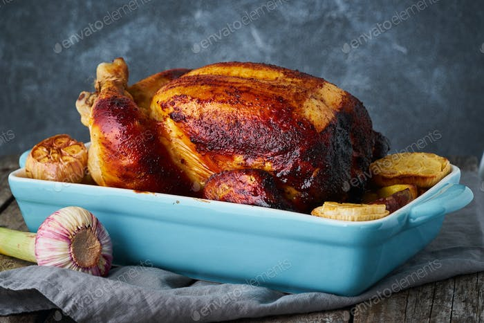 Roasted whole chicken in blue casserole on dark gray old wooden table