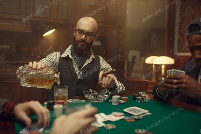 Poker player with cigar pours whiskey, casino