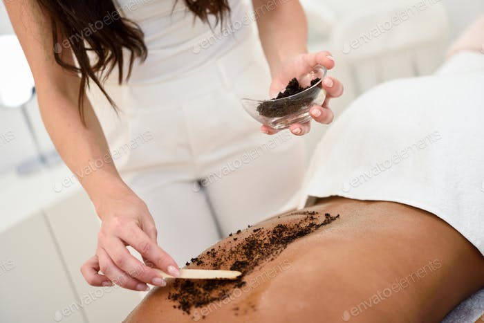 Woman cleans skin of the body with coffee scrub in spa wellness