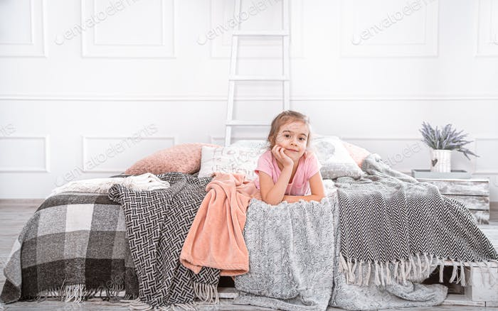 Cute little girl playing on the bed.