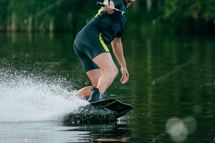 young man rides a wakeboard on lake