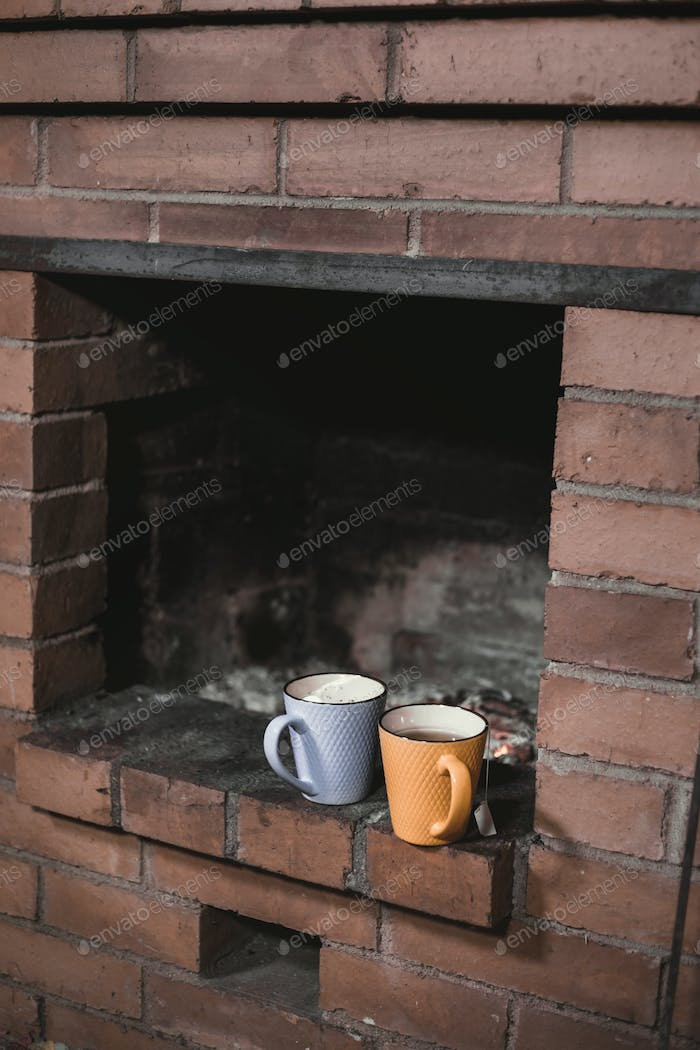Two cups with tea stand on a fireplace