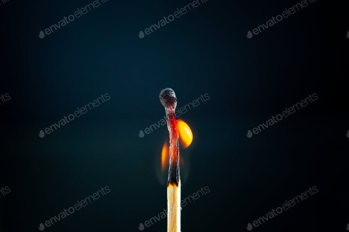 Front close view of half-burnt one match lighting on dark background