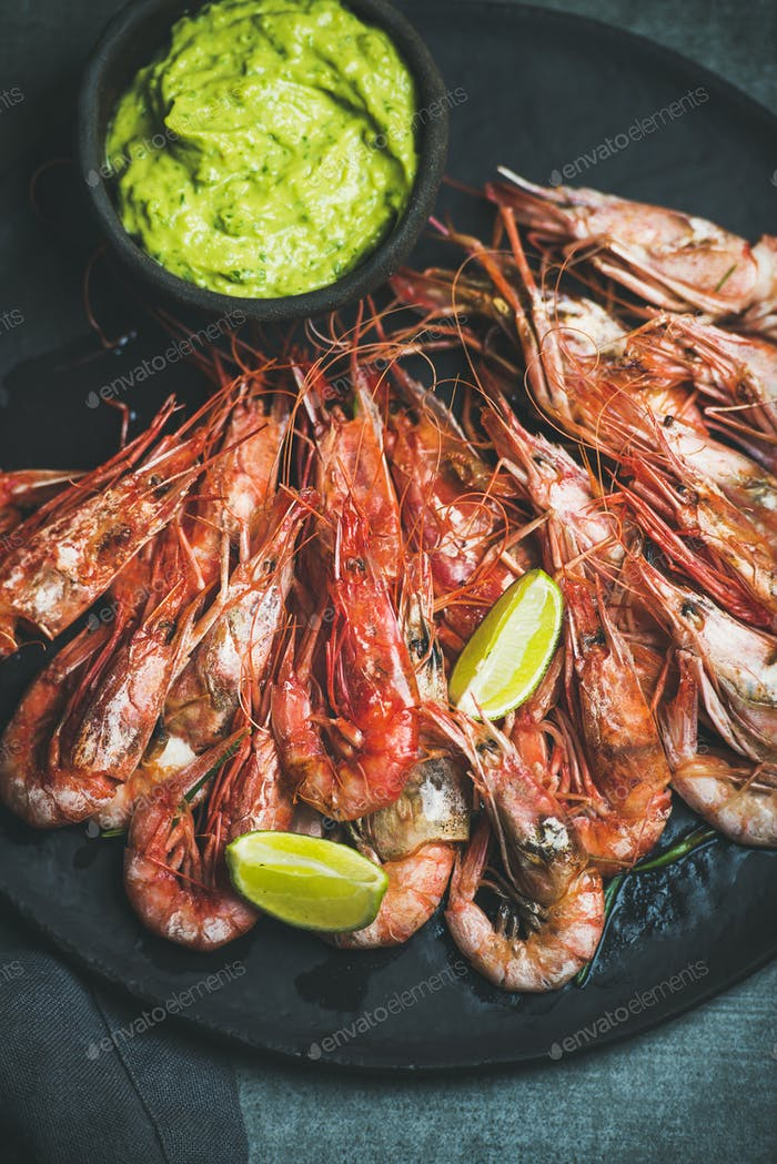 Roasted red shrimps with guacamole avocado sauce and lemon slices