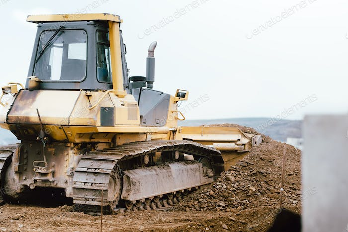 industrial construction site yellow bulldozer levelling and moving soil during highway building