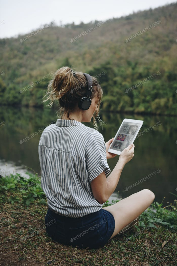 Woman alone in nature listening to music with headphones and digital tablet
