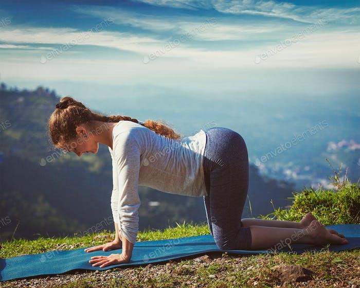 Sporty fit woman practices yoga asana bitilasana outdoors