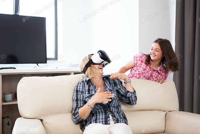 Happy middle aged woman with a VR headset on playing games