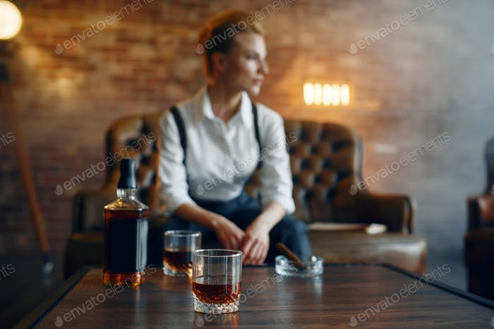 Woman in shirt and trousers with whiskey and cigar